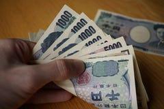 Mannelijke hand die Japanse munt (Yen) houden met zijn Aziatische symbolen in de vormbankbiljetten en hen terugtrekken van portef Royalty-vrije Stock Foto