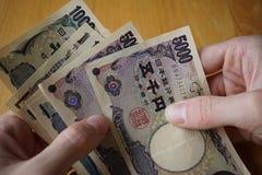 Mannelijke hand die Japanse munt (Yen) houden met zijn Aziatische symbolen in de vormbankbiljetten en hen terugtrekken van portef Stock Foto's