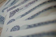 Mannelijke hand die Japanse munt (Yen) houden met zijn Aziatische symbolen in de vormbankbiljetten en hen terugtrekken van portef Stock Foto