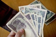 Mannelijke hand die Japanse munt (Yen) houden met zijn Aziatische symbolen in de vormbankbiljetten en hen terugtrekken van portef royalty-vrije stock afbeeldingen