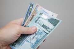 Mannelijke hand die Jordanian dinars houden royalty-vrije stock foto's