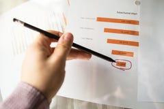 Mannelijke hand die met een potlood op een trechtergrafiek richten die op een wit blad van document tijdens een commerciële verga Royalty-vrije Stock Foto's