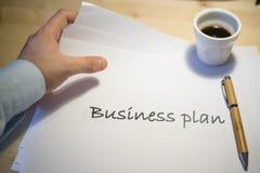 Mannelijke hand die op een businessplan richten die op een wit blad van document tijdens een commerciële vergadering wordt gedruk Royalty-vrije Stock Afbeelding