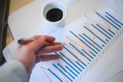 Mannelijke hand die op een gekleurde die kolomgrafiek richten op een wit blad van document tijdens een commerciële vergadering wo Stock Foto's