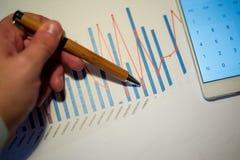 Mannelijke hand die op een kolomgrafiek richten die op een wit blad van document tijdens een commerciële vergadering wordt gedruk Stock Foto's