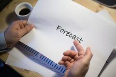 Mannelijke hand die op een voorspellingsdocument richten die op een wit blad van document tijdens een commerciële vergadering wor Royalty-vrije Stock Foto's
