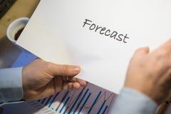 Mannelijke hand die op een voorspellingsdocument richten die op een wit blad van document tijdens een commerciële vergadering wor Stock Foto's