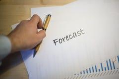 Mannelijke hand die op een voorspellingsdocument richten die op een wit blad van document tijdens een commerciële vergadering wor Stock Afbeeldingen