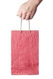 Mannelijke hand die rode die het winkelen zak houden op wit wordt geïsoleerd stock fotografie