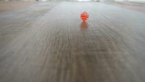 Mannelijke hand die rode kubus op grijze gelamineerde langzame motie spinnen stock footage