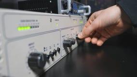 Mannelijke hand die van correcte ingenieur omhoog de volumeknoppen op het paneel van de controlemixer aanzwengelen Audioredacteur stock videobeelden