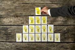 Mannelijke hand die witte kaarten met gele gloeilampen plaatsen in een vorm stock foto