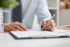 Mannelijke hand die zilveren pen klaar houden om nota te maken Stock Afbeeldingen