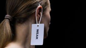 Mannelijke hand die zwak etiket op vrouwelijk oor hangen, die persoonlijke kwaliteiten onderstrepen stock video