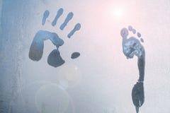 Mannelijke hand en voetdruk op bevroren venstersglas stock foto's