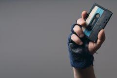 Mannelijke hand met handschoen die een oude muziekband houden Royalty-vrije Stock Fotografie