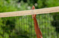 Mannelijke hand op het volleyball netto in het park stock foto's