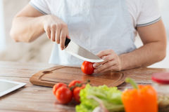 Mannelijke hand scherpe tomaat aan boord met mes Royalty-vrije Stock Foto's