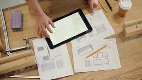Mannelijke hand wat betreft het tabletscherm met technische tekening van meubilair in workshop stock footage