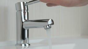 Mannelijke handen die chroom geplateerde kraan van water sluiten stock video