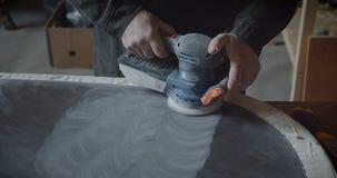 Mannelijke handen die de malende machine met behulp van om de houten raad op te poetsen en patronen op het te maken bij houten fa stock footage