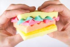 Mannelijke handen die een hamburger houden die van sponsen verschillende kleuren wordt gemaakt Concept ongezond voedsel en niet n Stock Foto