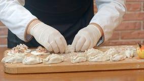 Mannelijke handen die eigengemaakte tortellini of de ravioli van het bollengebakje maken Model voor naar huis gemaakte die deegwa Stock Fotografie