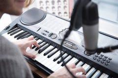 Mannelijke handen die elektronische piano spelen stock foto