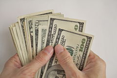 Mannelijke handen die en de stapel van Amerikaanse dollars Amerikaanse munt houden tellen, USD als symbool van bedrijfssucces Stock Foto