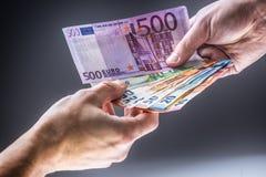 Mannelijke handen die euro bankbiljetten en de andere hand houden om een steekpenning te ontvangen royalty-vrije stock foto's