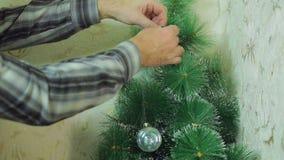 Mannelijke handen die feestelijke ballen op de Kerstboom hangen stock footage