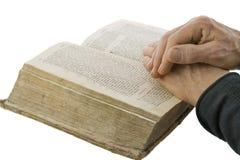 Mannelijke handen die in gebed op een open bijbel worden gesloten stock foto