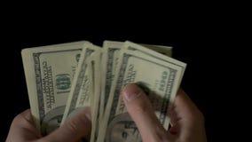 Mannelijke Handen die Geld, Honderd Dollarsrekeningen op zwarte tellen stock video