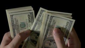 Mannelijke Handen die Geld, Honderd Dollarsrekeningen op zwarte tellen stock footage