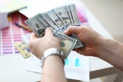 Mannelijke handen die geld van reusachtig pak tellen stock foto's