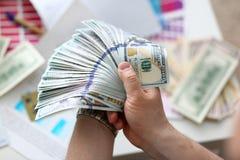 Mannelijke handen die geld van reusachtig pak tellen stock fotografie