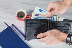 Mannelijke handen die het zwarte hoogtepunt van de leerportefeuille van euro rekeningen op gr. houden Stock Foto