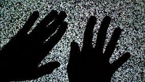 Mannelijke handen die op het TV-scherm met statisch televisielawaai als achtergrond kruipen stock footage