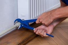 Mannelijke handen die radiator herstellen Royalty-vrije Stock Afbeeldingen