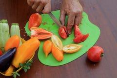 Mannelijke handen die rijpe tomaten snijden in plakken op scherpe raad C Stock Foto