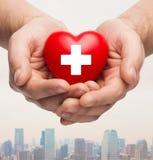 Mannelijke handen die rood hart met wit kruis houden royalty-vrije stock foto