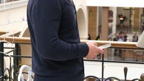 Mannelijke handen die smartphone in winkelcomplex gebruiken Close-up van mens het doorbladeren informatie en het scrollen beelden stock footage
