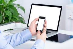 Mannelijke handen die smartphonemodel gebruiken bij het bureau Stock Afbeeldingen