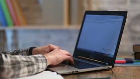 Mannelijke handen die tekst op modern laptop toetsenbord typen stock footage