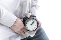 Mannelijke handen die wekker op gezondheid de als achtergrond van witte Mensen houden stock foto's