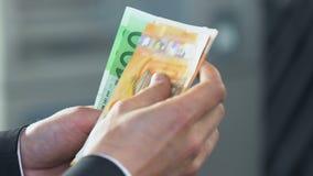 Mannelijke handen die zijn salaris verhalen, die euro rekeningen, besnoeiing op de begroting en economie houden stock video