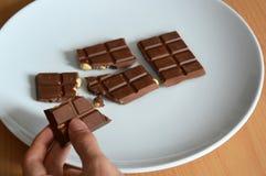Mannelijke handen gebarsten chocoladereep op een plaat stock afbeelding