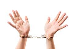 Mannelijke handen op een wit close-up als achtergrond in handcuffs royalty-vrije stock afbeelding