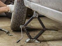 Mannelijke handen van het wiel met een bruine auto in de garage Stock Foto's