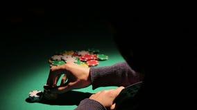 Mannelijke het gokken verslaafde het spelen pook bij onwettig casino, die risico nemen om geld te verliezen stock videobeelden